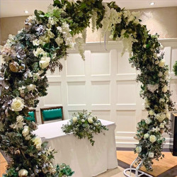 circle of love arch with foliage and flowers to hire