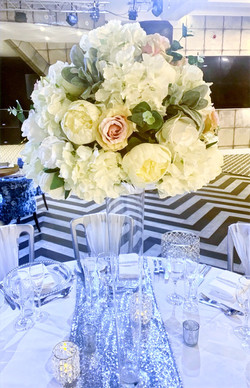tall glass vases with arrangements of flowers