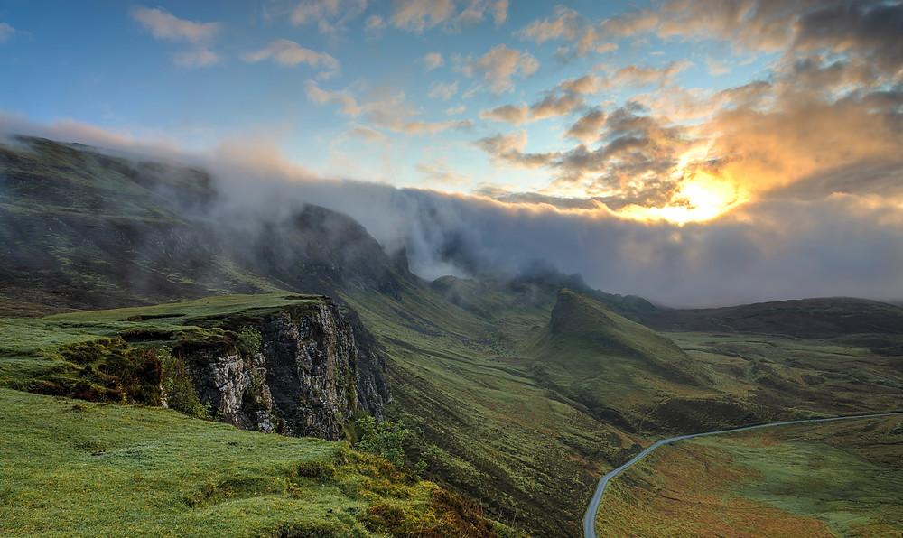 Pathway leading through mountains towards the sunrise.