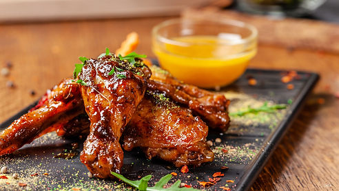 The concept of Indian cuisine. Baked chicken wings and legs in honey mustard sauce. Servin
