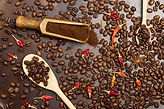 Ground coffee in wooden scoop. Roasted coffee beans in spoon. Roasted coffee beans on tabl