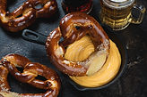 Cast-iron pan with cheese dip, pretzels and beer, studio shot on a dark brown stone backgr