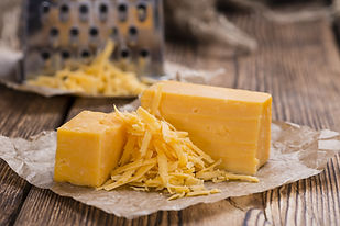 Cheddar Cheese (grated) as close-up shot on an old vintage wooden table.jpg
