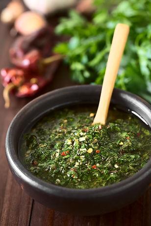 Raw homemade Argentinian green Chimichurri salsa or sauce made of parsley, garlic, oregano