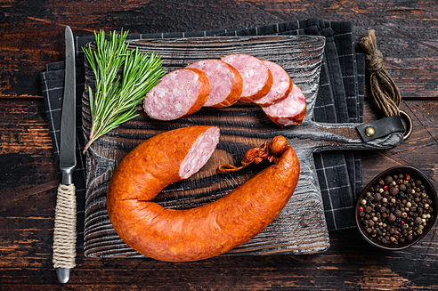 German Smoked sausage on a wooden rustic board with thyme. Dark wooden background. Top vie