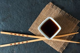 Close up of chopsticks resting on a small bowl of asian dipping sauce..jpg