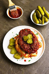 Tasty nashville hot chicken sandwich on plate over brown stone background. .jpg