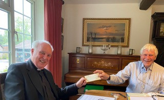 Father John Caperon receiving a cheque from Richard Thorne one of the Trustees of the Friends of Christ Church