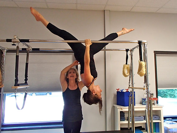 Pilates instructor assisting client.