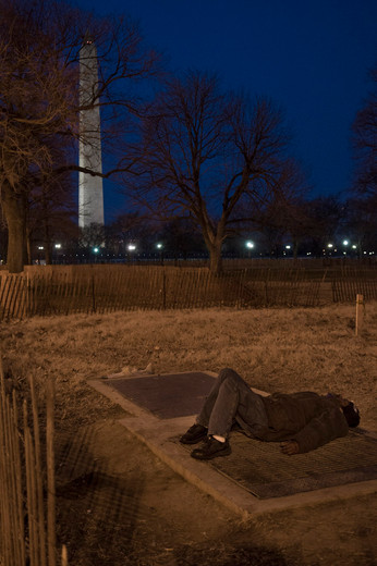 A homeless man sleeps by a ventilation shaft. Washington DC, 2009.
