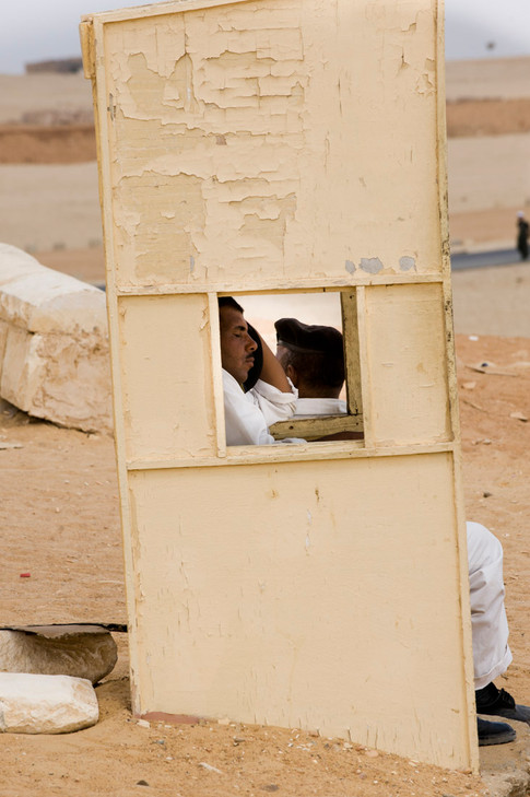 An antiquities policeman falls asleep on the job by the Giza pyramids in Egypt. 2009.