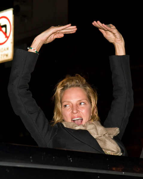Uma Thurman rejoices from her sunroof on 125th Boulevard in Harlem.