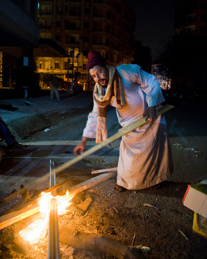The vigils use crates, boxes and wooden beams to feed their fires through the night.