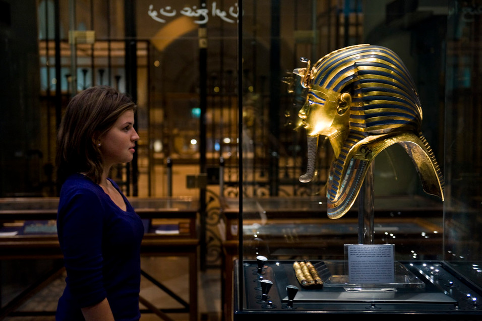 An American woman stands in awe before the mask of Tutankhamen. 2009.
