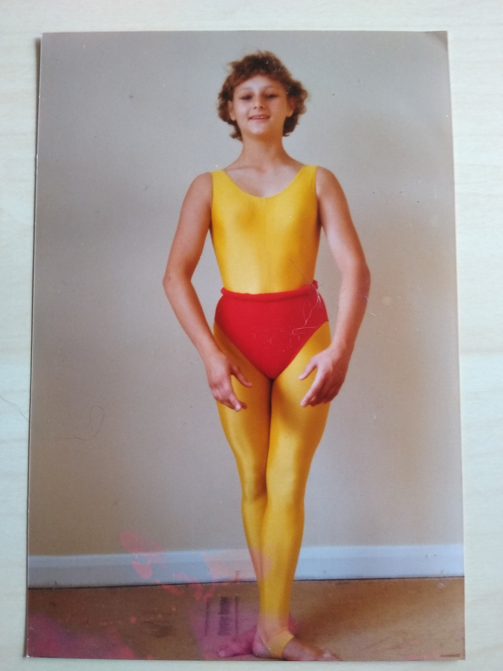 Young woman in yellow and read leotard / catsuit.