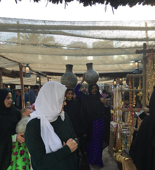 Qasr Al Hosn Festival emirati ladies in old souk with water jars on their heads