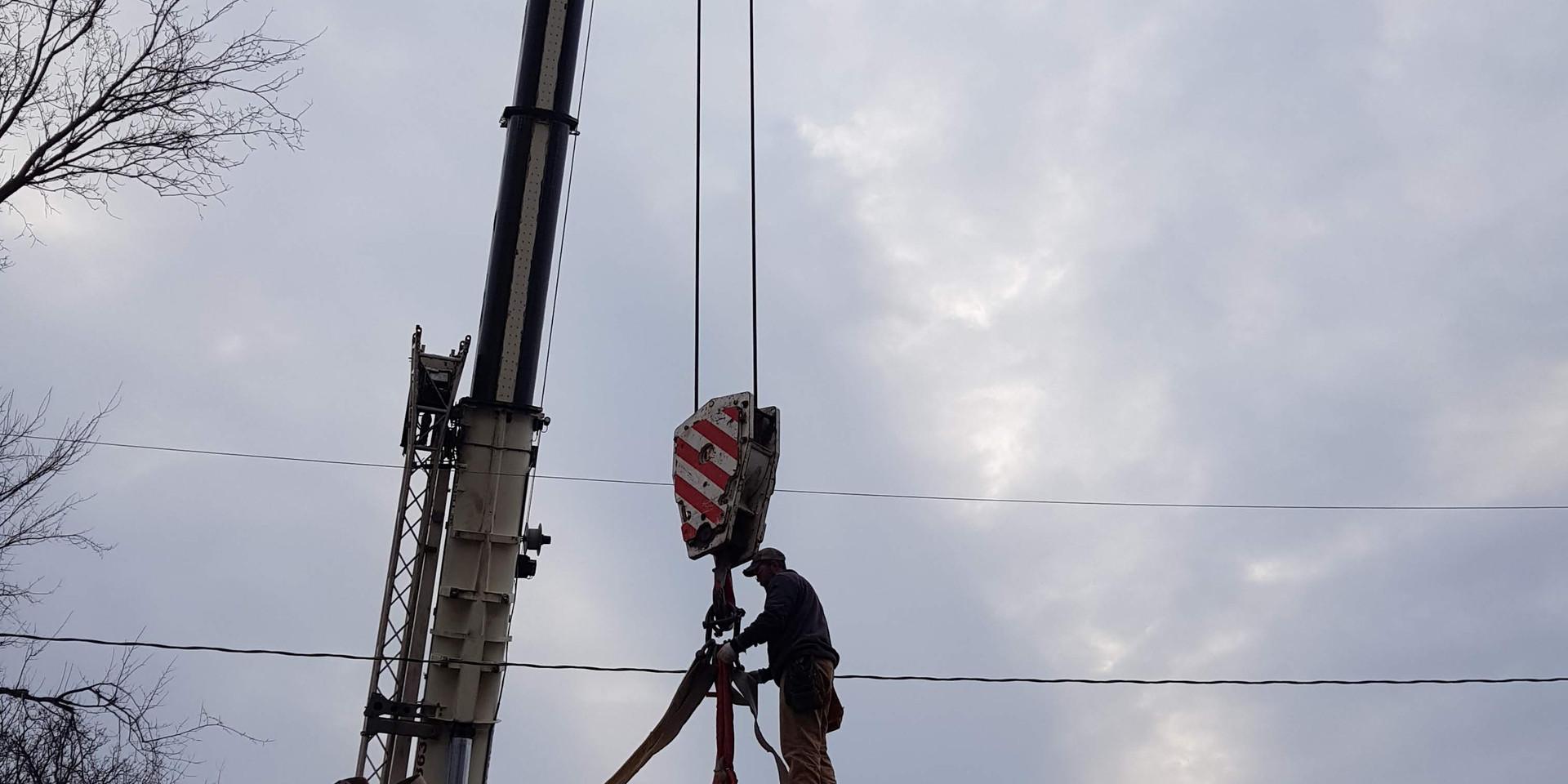 Set crew hooking up crane to first mod.