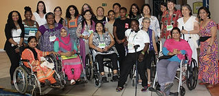 Diverse group of women, many with disabilities from around the globe wearing colorful clothing. Wheelchair users in the front row with others standing behind.