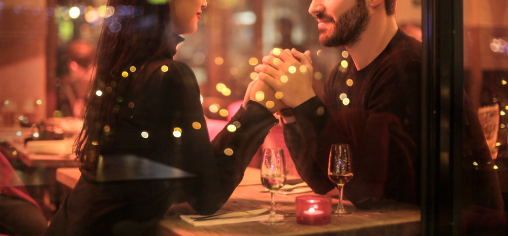 couple holding hands at a table