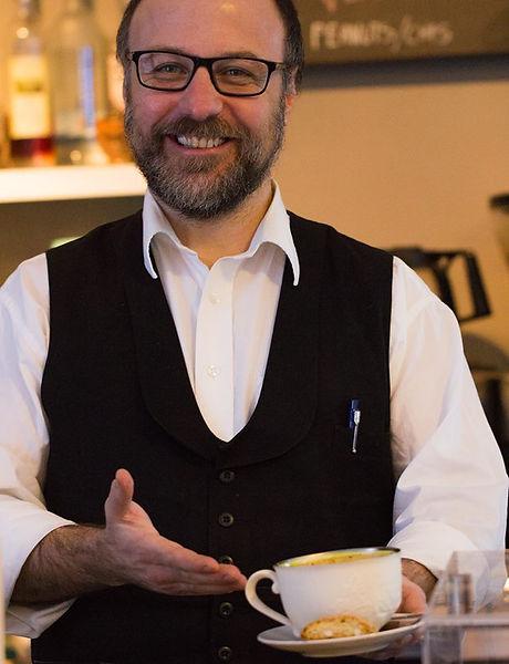 Christian Alves De Carvalho Rasmussen smilende forran disken på Lumen café & restaurant  stokke