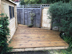 Curved decking built, round hole for plant. Raised decking, new shed and gate fitted.