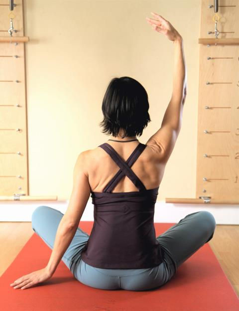 A Pilates shoulder stretch in front of Pilates springboards