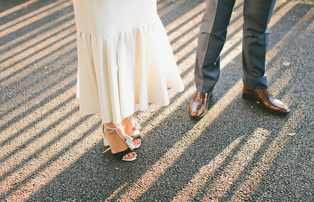 Bride and groom high heels and dress shoes in sunlight at engagement party.
