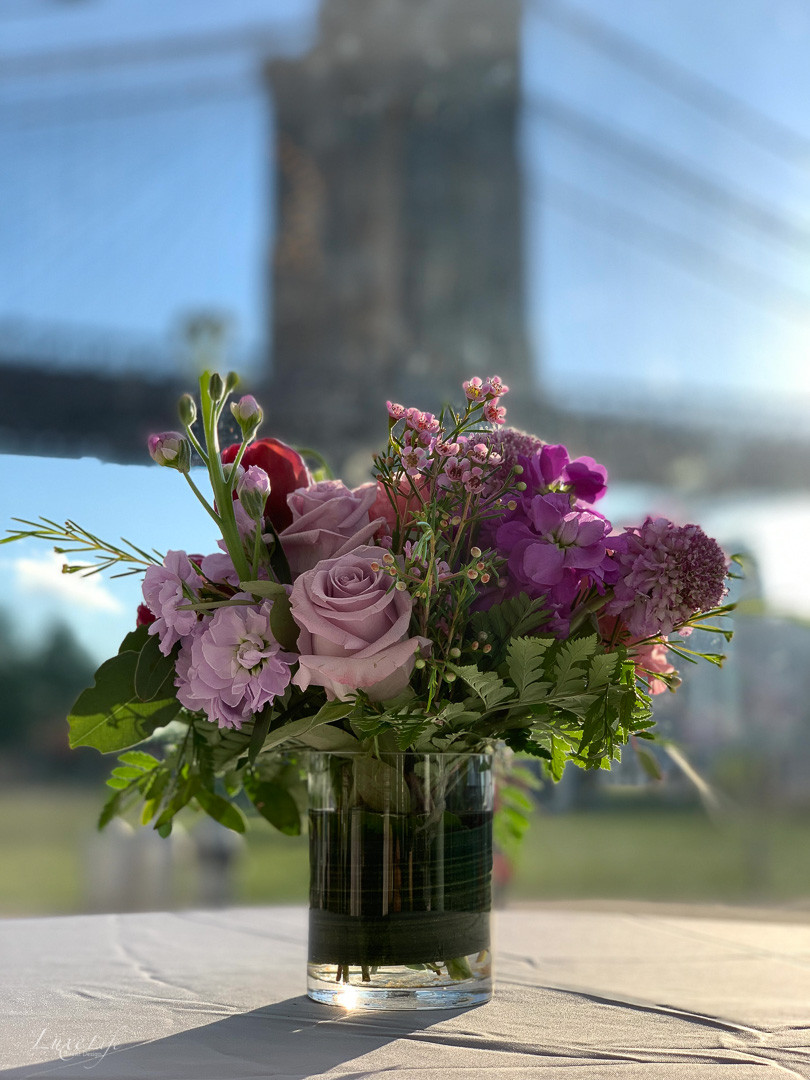 Flower arrangement in front of Brooklyn Bridge at Jane's Carousel for a wedding planned, coordinated and designed by Luxe Life Event Design.