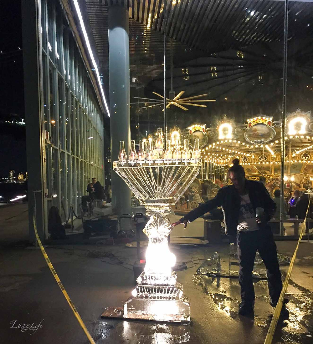 Custom carved ice menorah for a Hanukkah holiday party at Jane's Carousel in Dumbo Brooklyn, New York. Event planned, coordinated and designed by Luxe Life Event Design.
