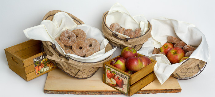 Fall tablescape of apple cider doughnuts and apples in baskets and crates. Photo by The Luxe Life Event Design.