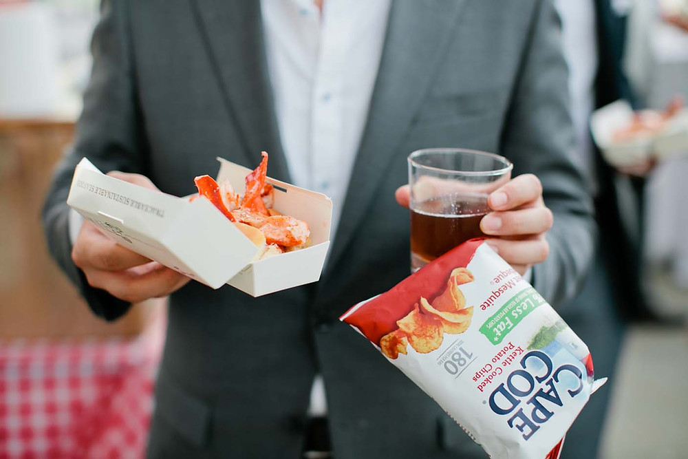 Wedding-guest-holding-a-lobster-roll,-drink-and-chips.