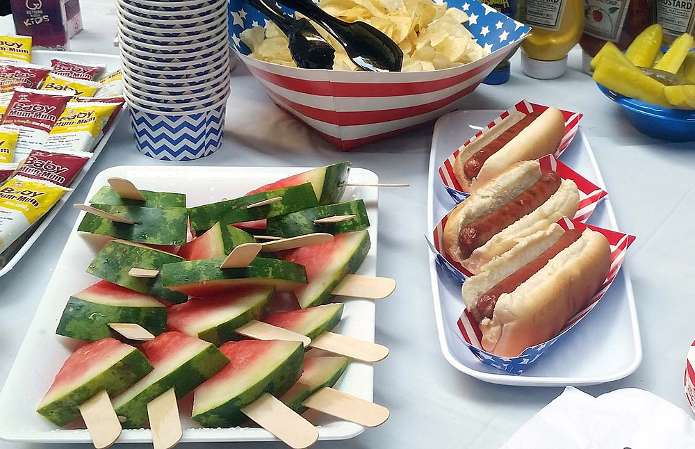 Watermelon and hot dogs in patriotic tablescape.