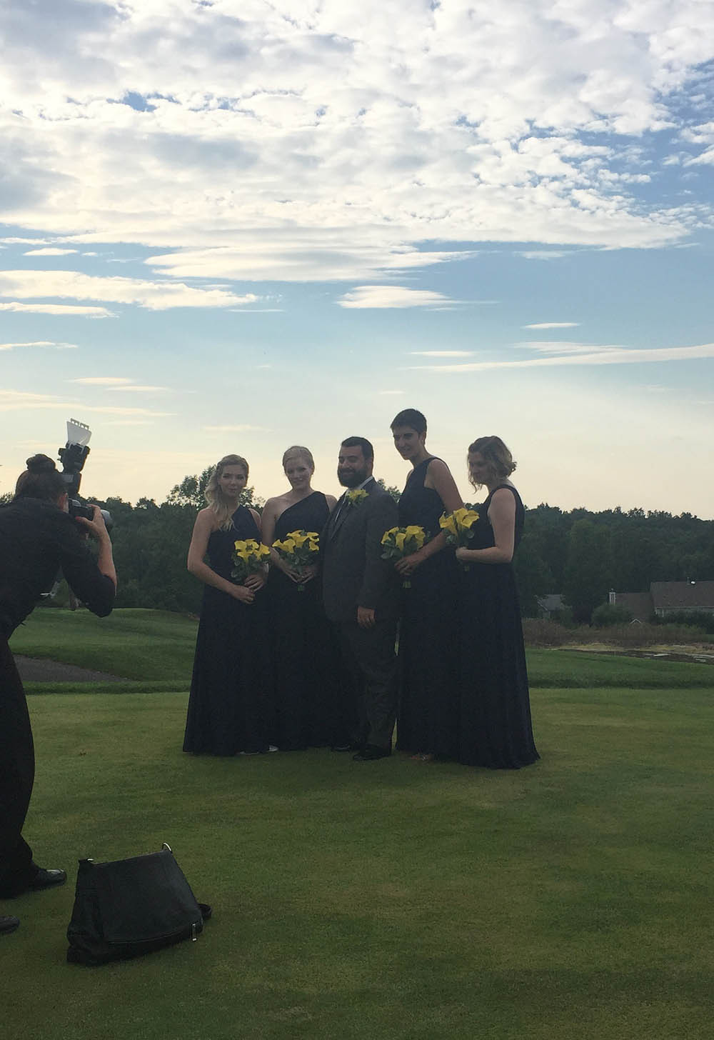 Bridesmaids having pictures taken with groom.