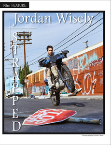 "Jordan Wiseley doing a ""wheely"" on his motorcycle.  There is a downed stop sign lying on the street and a wall of grafiti in the background.."