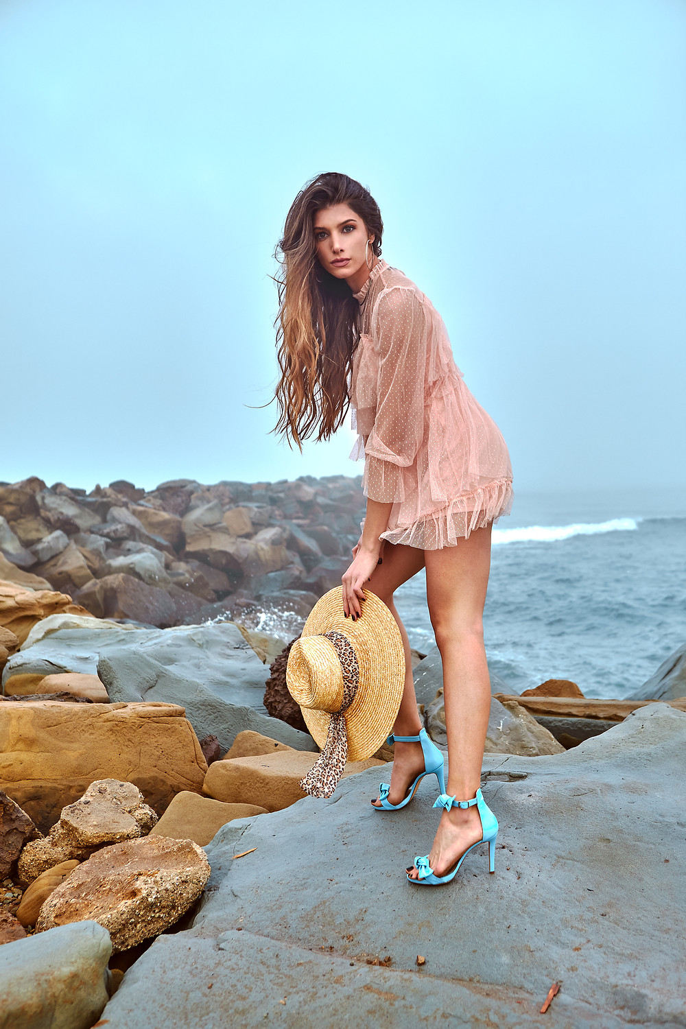Fashion portrait of model Sofija Stojkovic at Aston Models in Los Angeles, California wearing a pink beach dress, baby blue heels, and a straw hat with a leopard sash.