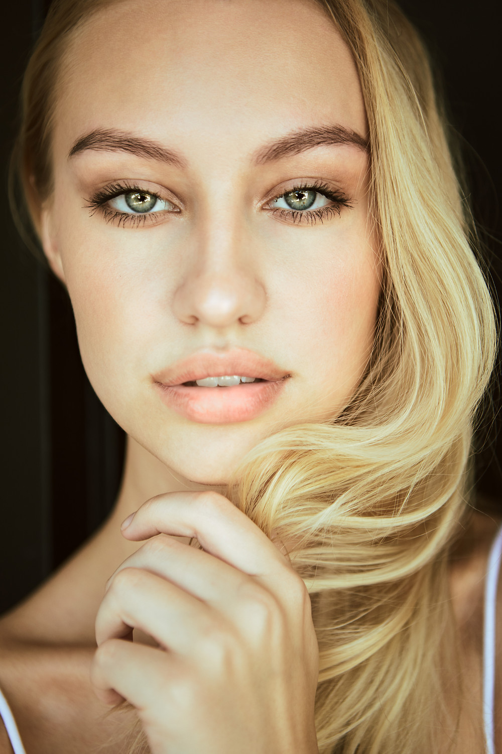 Swedish model Emelie MacInnes poses for a beauty photograph with striking green eyes, long blonde hair to one side, and soft natural lips by Los Angeles fashion photographer Patrick Patton.
