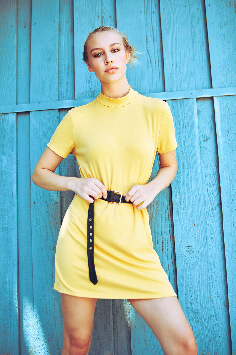 Swedish Model Emelie MacInnes wears a yellow dress in front of a blue wall with a black belt, striking blue eyes, and blonde hair up in a bun by Los Angeles fashion photographer Patrick Patton.