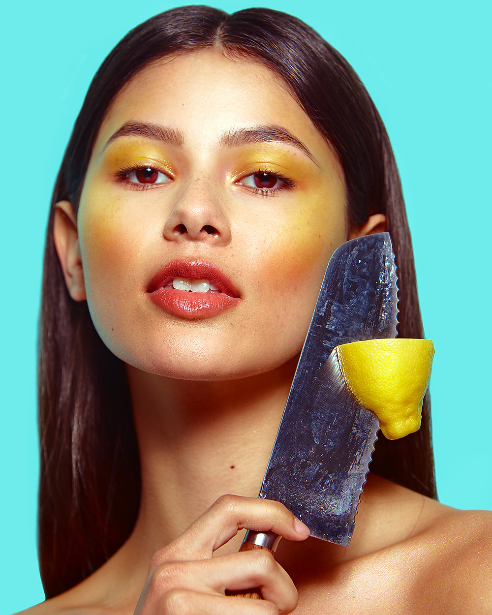 Model Genevieve van Dam holds a knife and a lemon in a fruit-inspired beauty editorial photo shoot published in New Face Fashion Magazine and photographed by commercial and fashion photographer Patrick Patton.