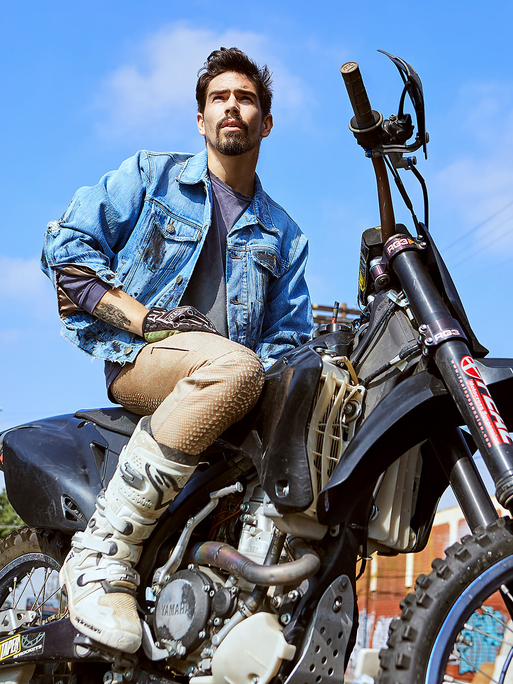 Jordan sits on his motorcycle wearing clothes that he designed for Strapped Mfg. with a big, blue sky in the background
