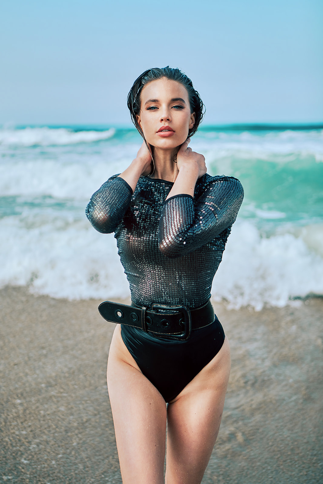 Model Egith Van Dinther aka Iggy Van D poses in the ocean wearing a sheer sequin long-sleeve Free People top and black bikini bottoms for New Face Fashion Magazine by photographer Patrick Patton