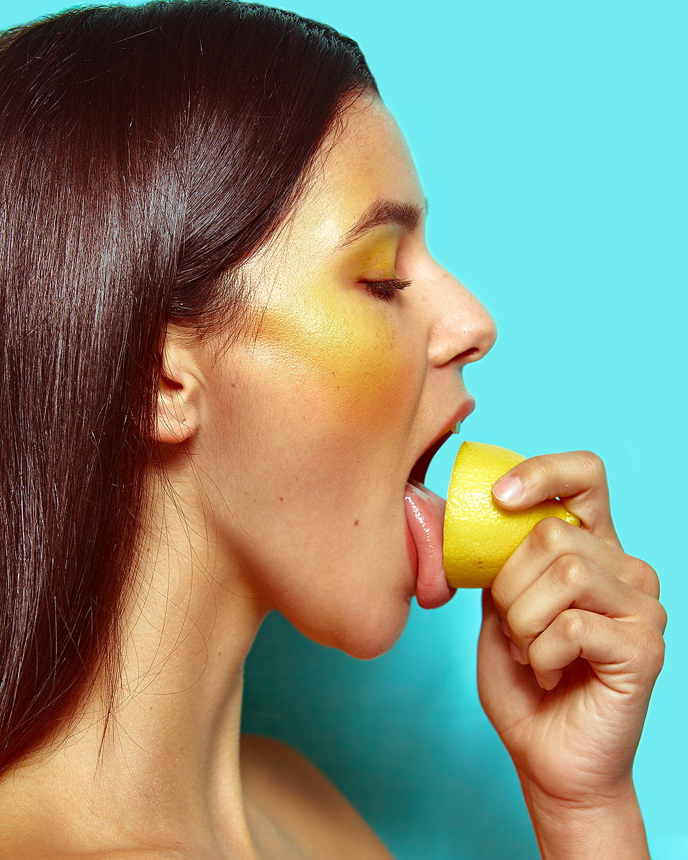 Model Genevieve van Dam licks a lemon in a fruit-inspired beauty editorial photo shoot published in New Face Fashion Magazine and photographed by commercial and fashion photographer Patrick Patton.