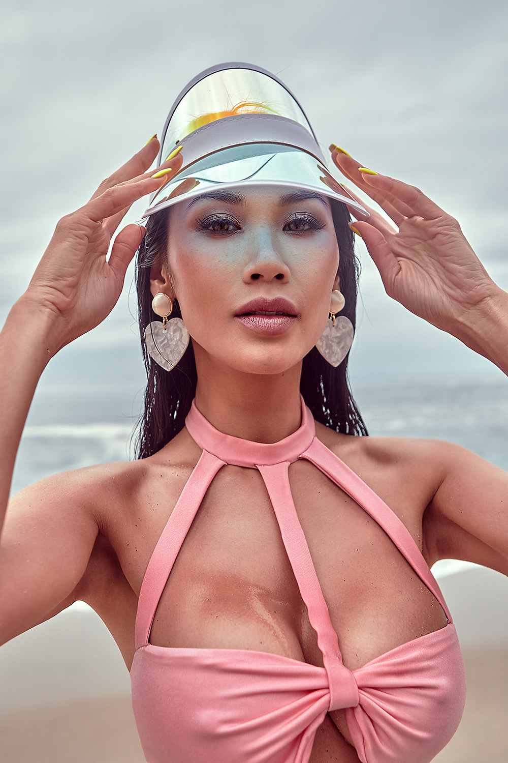 Model and fashion influencer Claire Reine Godard poses in a translucent visor and strappy pink bikini on the sand in Laguna Beach for a swimwear editorial shot by Patrick Patton for New Face Magazine July 2019.