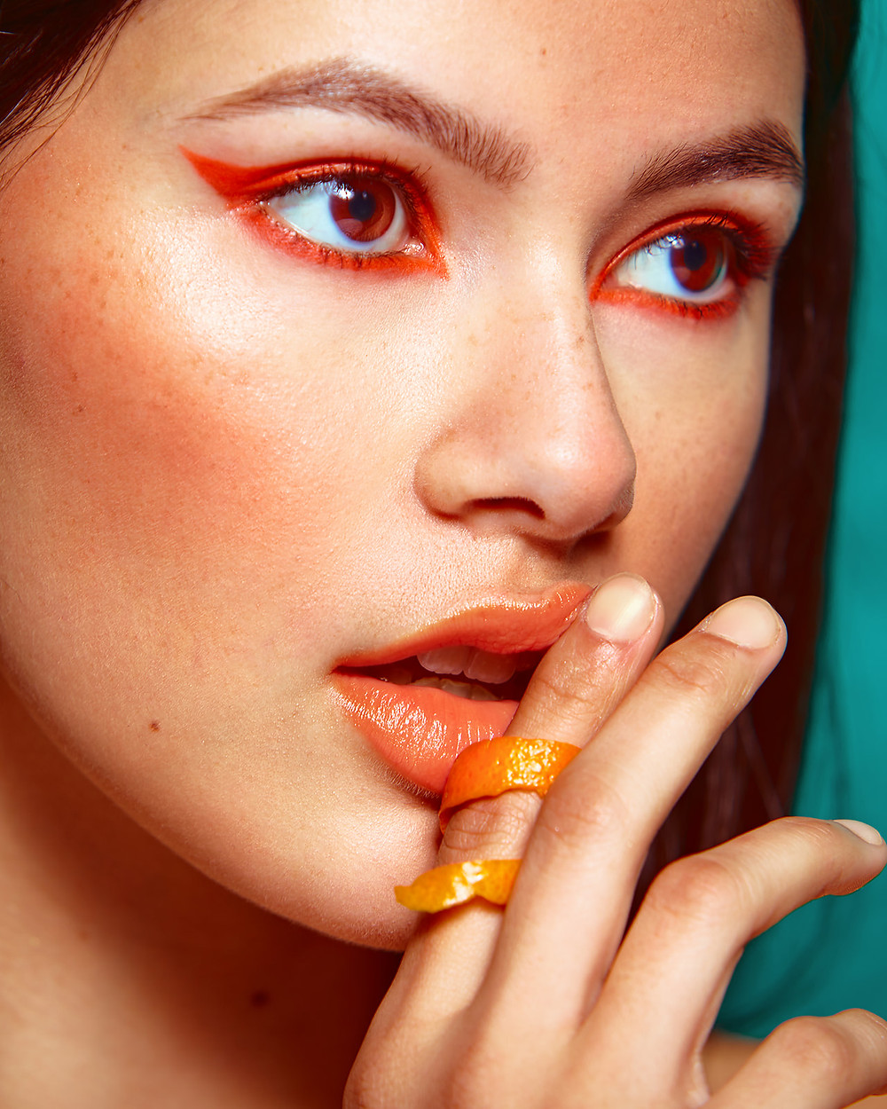Model Genevieve van Dam wears an orange peel ring on her finger in a fruit-inspired beauty editorial photo shoot published in New Face Fashion Magazine and photographed by commercial and fashion photographer Patrick Patton.