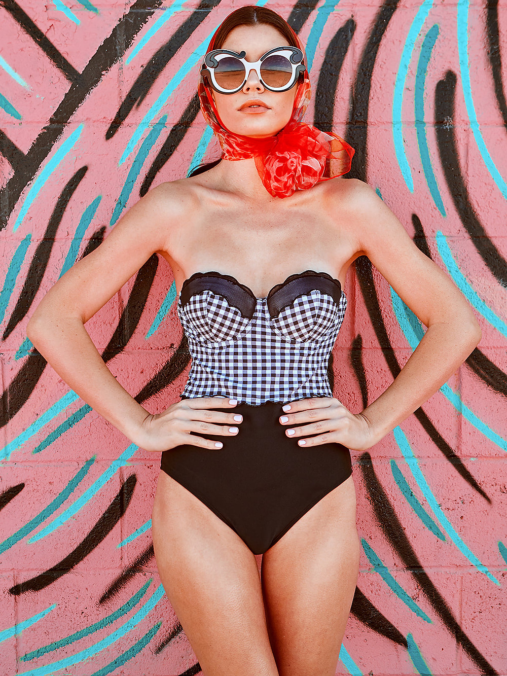 Los Angeles swimwear model Gracie Phillips wears a black and white gingham onepiece swimsuit by Betsy Johnson, swirl sunglasses by Prada, and a red vintage 1950's headscarf for a retro swim fashion photoshoot.