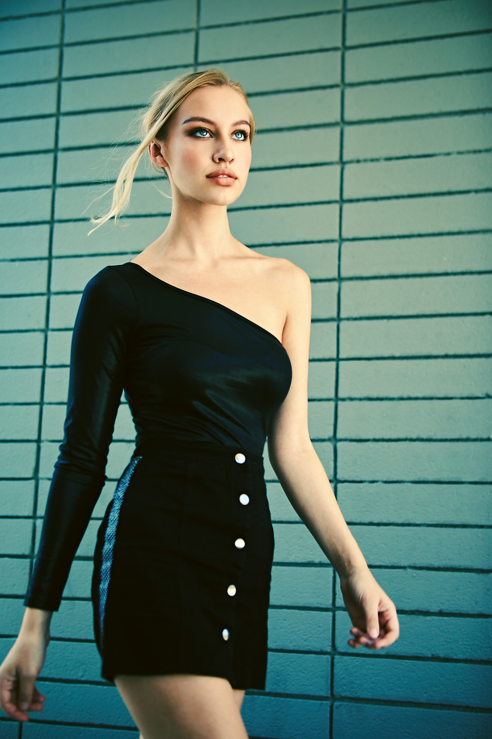 Swedish model Emelie MacInnes walks through the streets of Hollywood and poses in a fashion-forward black top and skirt with striking blue eyes and blonde hair blowing in the wind by Los Angeles fashion photographer Patrick Patton.