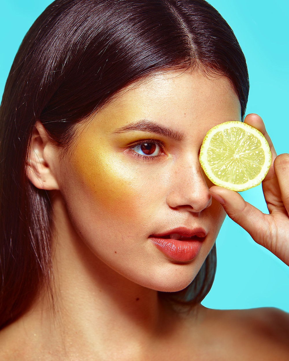 Model Genevieve van Dam holds a lemon over her eye in a fruit-inspired beauty editorial photo shoot published in New Face Fashion Magazine and photographed by commercial and fashion photographer Patrick Patton.