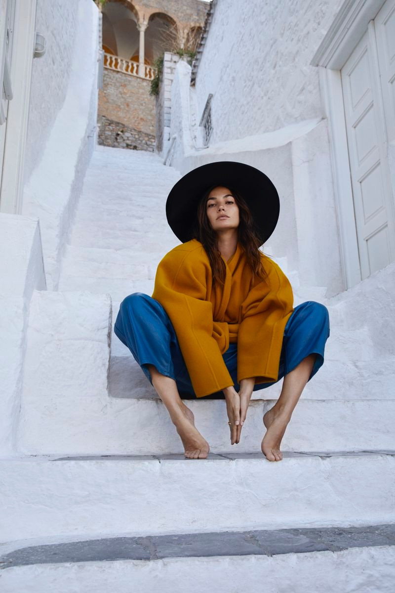 Lily Aldridge modeling blue pants and a yellow coat and a black hat on white steps in Hydra, Greece.
