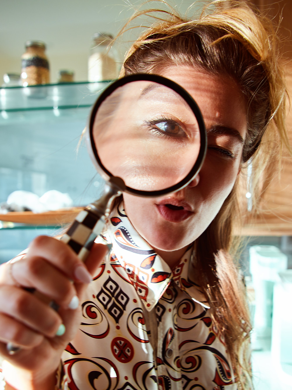 Tori Deal of SuiHeart Club looks through a magnifying glass.  Photography by Patrick Patton.