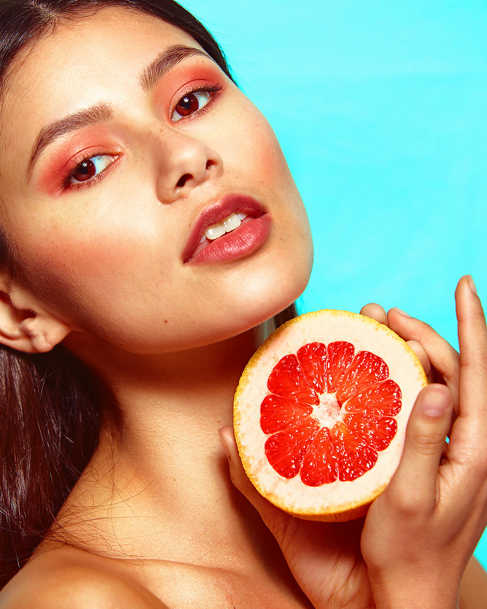 Model Genevieve van Dam holds sliced grapefruits in a fruit-inspired beauty editorial photo shoot published in New Face Fashion Magazine and photographed by commercial and fashion photographer Patrick Patton.
