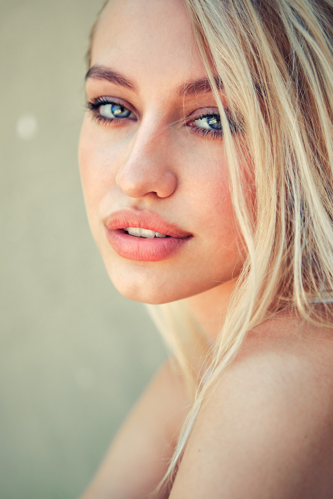 """Reminiscent of Angelina Jolie's blonde look from the film """"Gone In 60 Seconds"""", Swedish Model Emelie MacInnes poses with big lips, striking blue eyes, and blonde hair falling softly on her face in a beauty portrait by Los Angeles fashion photographer Patrick Patton."""